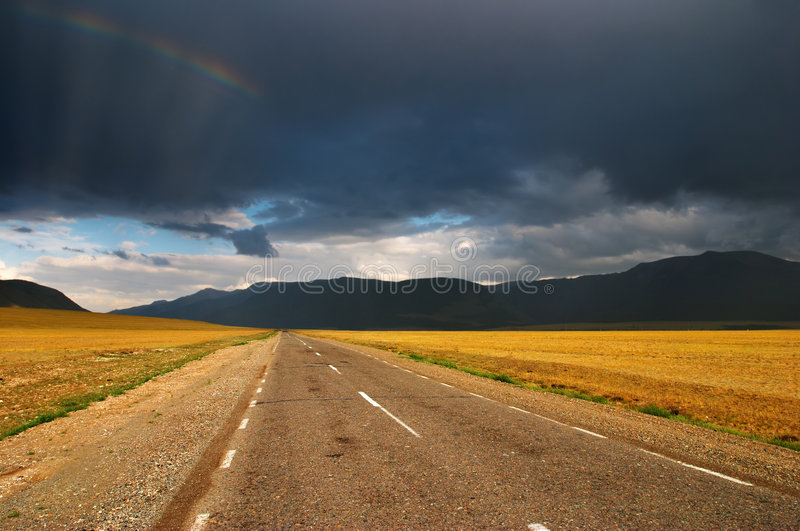 Rainbow over road. Landscape with road and storm clouds stock photography