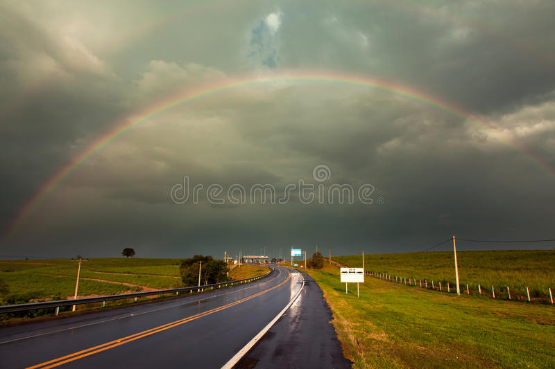 Rainbow over a road. Rainbow after a storm in a wet highway stock photography