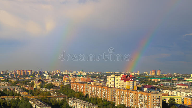 Rainbow over the roofs of Omsk stock photos