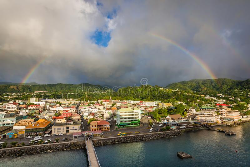 A rainbow over Roseau, Dominica. A thunderstorm breaks and produces twin rainbows over the vibrant coastal city royalty free stock photos