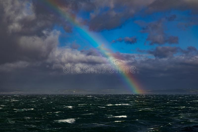 Rainbow Over Rough Seas In The English Channel. Rough seas in the English Channel with a colorful rainbow and France in the background. Photo taken from a royalty free stock images