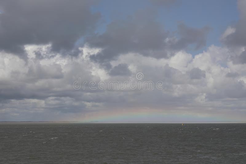 Rainbow over the sea with clouds on sky royalty free stock photo