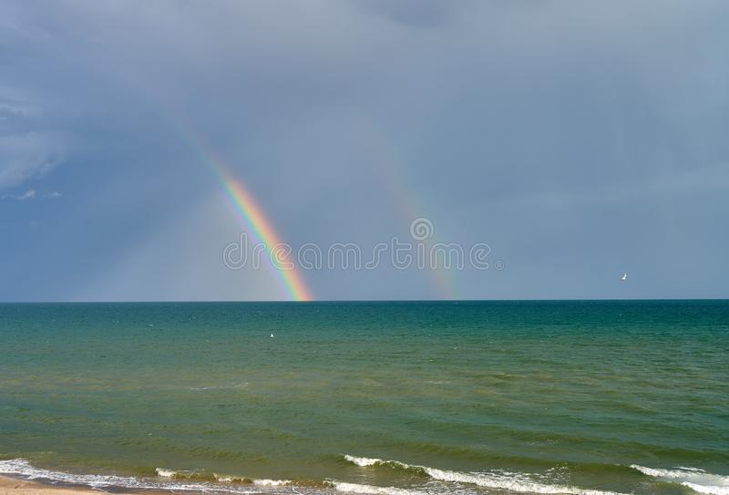 Rainbow over the sea, the shore of the Sea of Azov. Storm on the sea, the shore of the Sea of Azov royalty free stock images