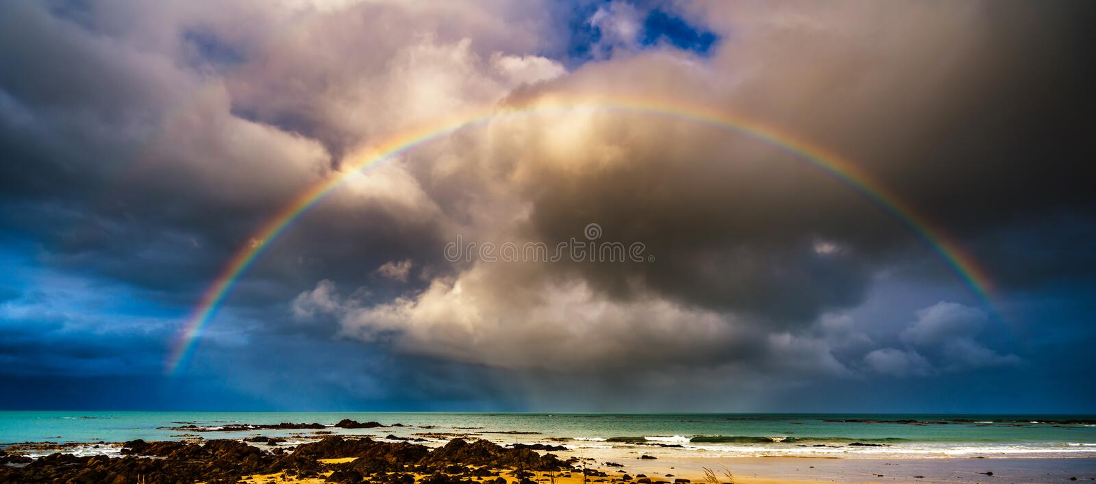 Rainbow over the Sea. After storm, sunshine comes again, we see beautiful rainbow over the sea, New Zealand royalty free stock photography