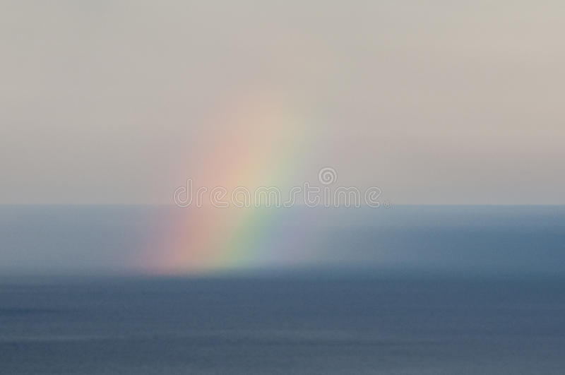 Rainbow over sea water royalty free stock photo