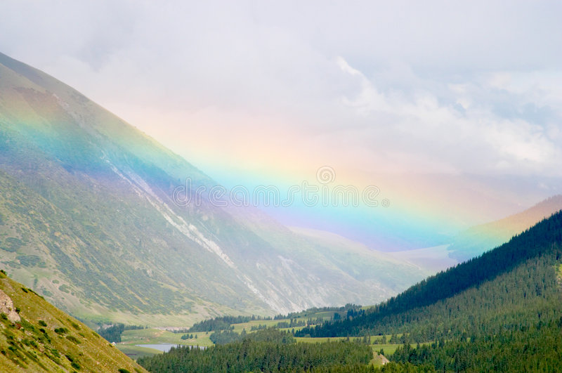 Rainbow over the valley royalty free stock photo