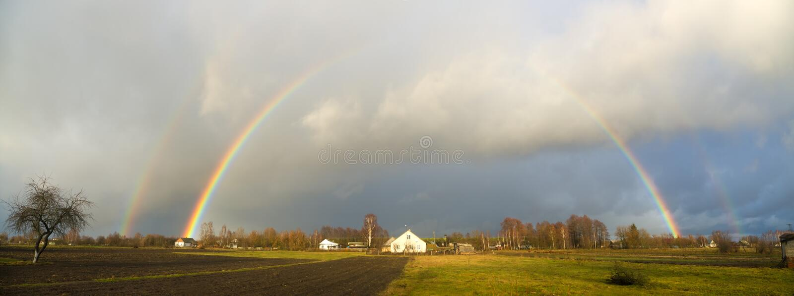 Rainbow over the village royalty free stock photo