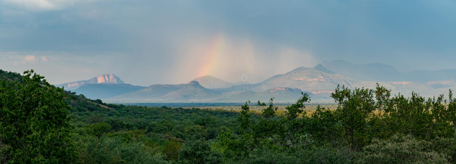 Rainbow over the Waterberg Mountains in South Africa. Panoramic view to a rainbow behind the Waterberg Mountains in South Africa stock photo