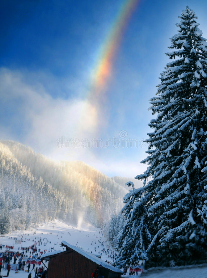 Rainbow over wintry landscape stock images