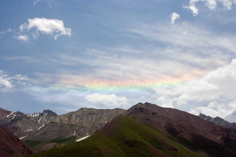 Rainbow in Pamir mountains. Rainbow in mountains of Pamir in summer day stock images