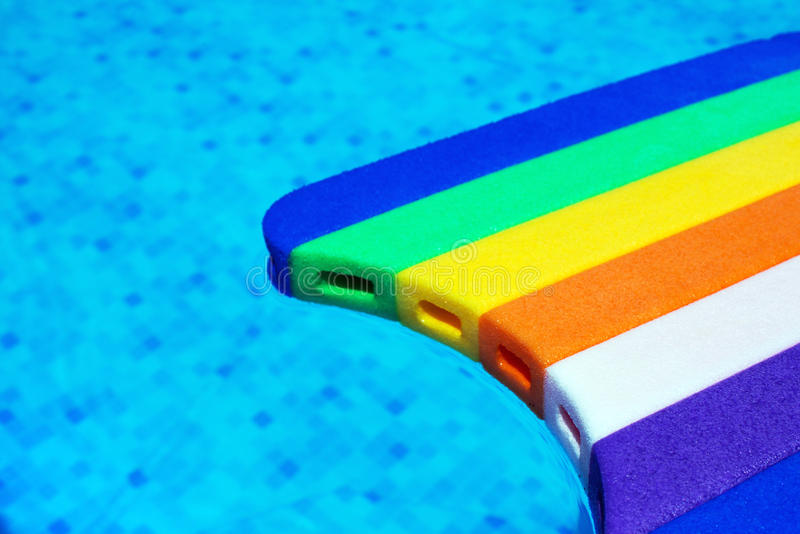 Rainbow pattern styrofoam swimming board baseboard floating in p. Rainbow pattern styrofoam swimming board or baseboard floating in swimming pool water royalty free stock images