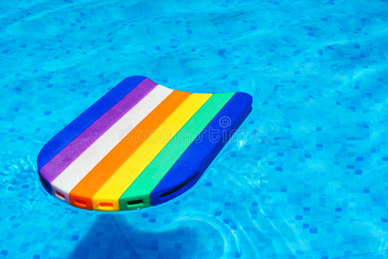 Rainbow pattern styrofoam swimming board baseboard. Rainbow pattern styrofoam swimming board or baseboard floating in swimming pool water, summertime vacation royalty free stock images