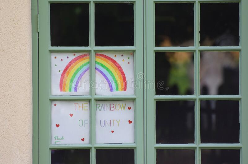 A rainbow picture in a window during the coronavirus /  COVID-19 pandemic May 2020 royalty free stock image