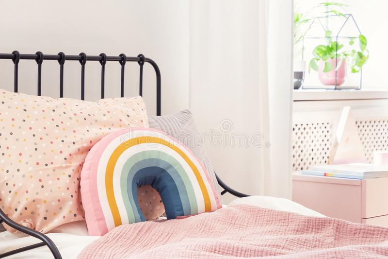 Rainbow pillow and pink sheets on girl`s bed in bright bedroom interior with plant. Real photo stock photo