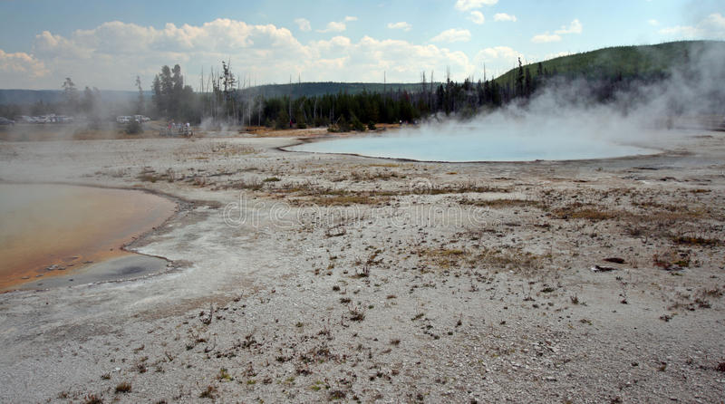 Rainbow Pool hot spring and Sunset Lake geyser in Black Sand Basin in Yellowstone National Park in Wyoming USA royalty free stock photography