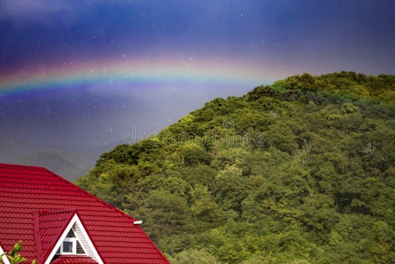 Rainbow after rain over the house royalty free stock photos