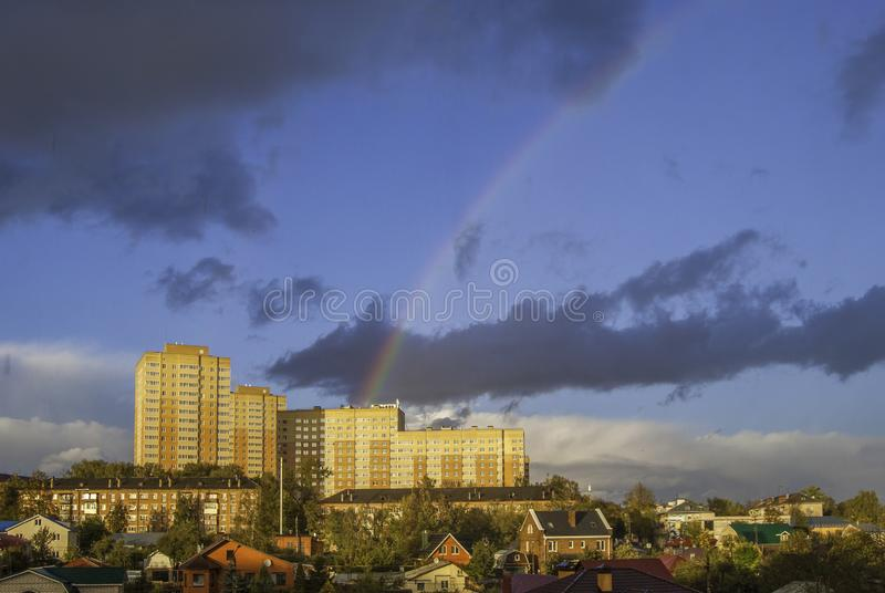 Rainbow after rain over the houses in the city stock photo
