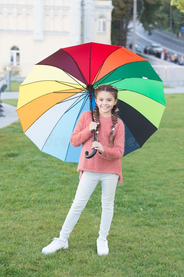 Rainbow after rain. Positive mood in autumn rainy weather. Optimist and cheerful child. Spring style. Little girl under. Colorful umbrella. Multicolored royalty free stock images