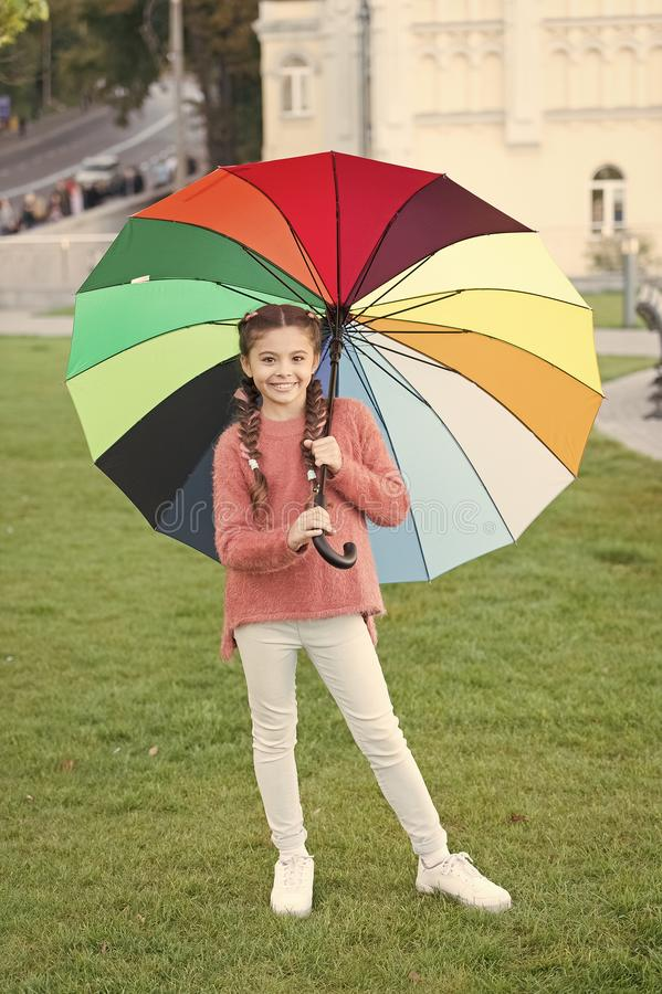 Rainbow after rain. Positive mood in autumn rainy weather. Optimist and cheerful child. Spring style. Little girl under. Colorful umbrella. Multicolored stock photo