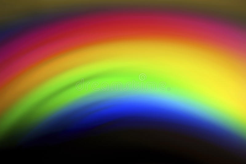 Rainbow Reflection from CDROM. A Rainbow of Colour via a Reflection from a CDROM Surface. A blurred cascade of bright colours set to a dark backdrop stock photography
