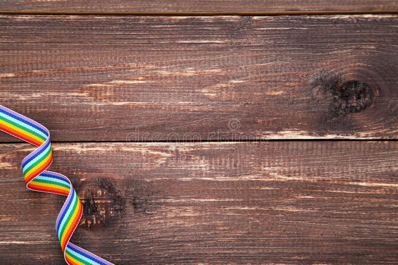 Rainbow ribbon. On brown wooden table stock photography
