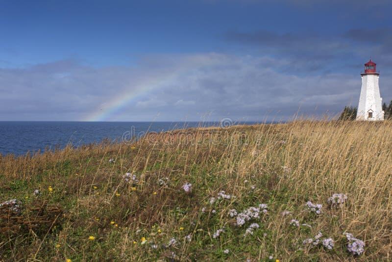 Rainbow at Seacow Head lighthouse, Prince Edward Island. Rainbow over ocean at Seacow Head lighthouse, Prince Edward Island, Canada stock images