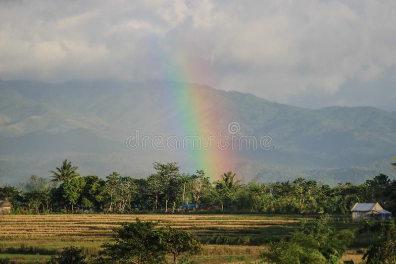 Rainbow in a farm in the Philippines. A rainbow showing from afar near the trees and mountain in Camarines Sur, Philippines royalty free stock images