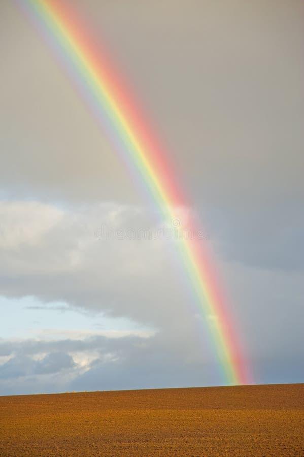 Rainbow sopra sbarco di recente arato. fotografie stock