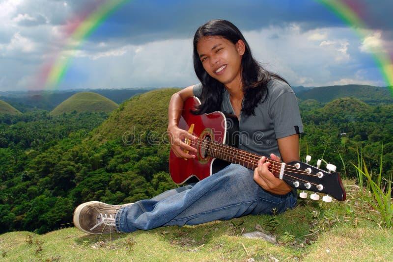 Rainbow sorridente del giocatore di chitarra u fotografia stock