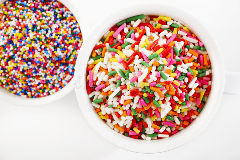 Rainbow sprinkles. In white cup royalty free stock photography