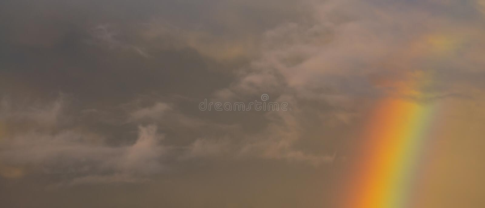 Rainbow at Sunset with a Cloudy Sky. royalty free stock image