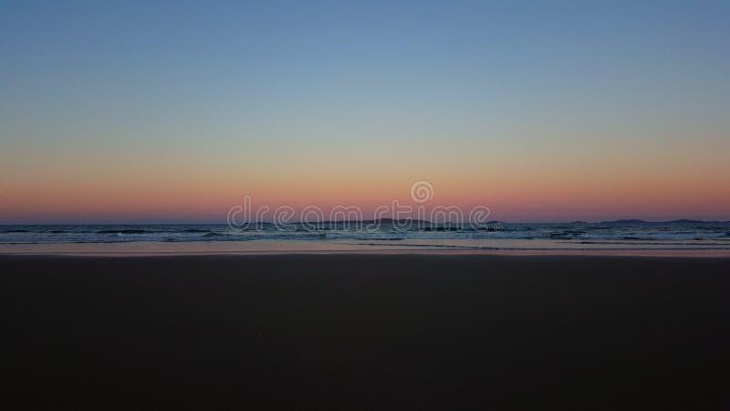 Rainbow sunset and ocean stock photography