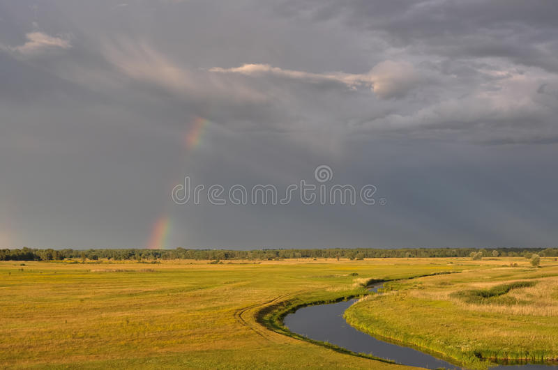 Rainbow after a thunderstorm at sunset. Gray saturated sky and yellow grass in the meadow. River View stock photos