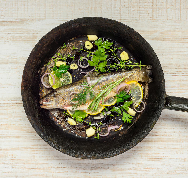Rainbow Trout Fish in Frying Pan with Herbs and Spices royalty free stock image