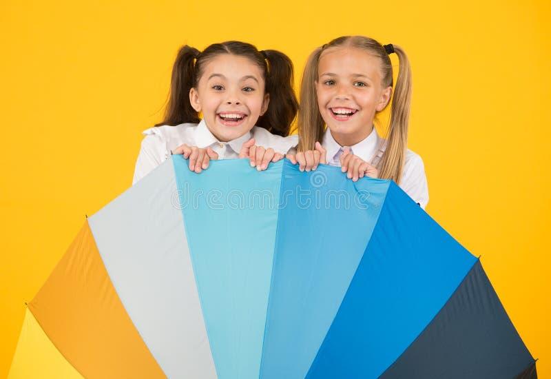 Rainbow umbrella. Colorful life. Schoolgirls happy big umbrella. Fall weather forecast. Place for both of us. Fashion royalty free stock photo