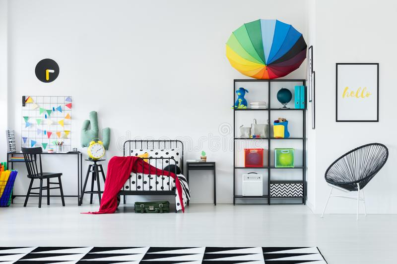 Rainbow umbrella on rack. Rainbow umbrella placed on a black metal rack standing in a white room with bed for kid royalty free stock photo