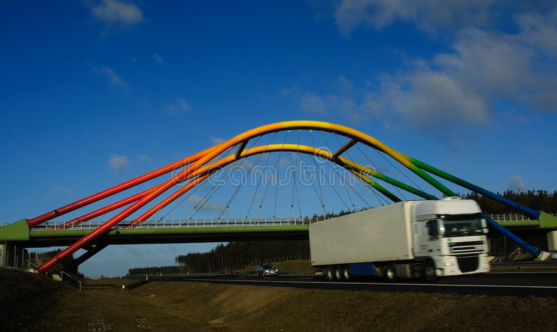 Rainbow viaduct over highway with truck moving royalty free stock image