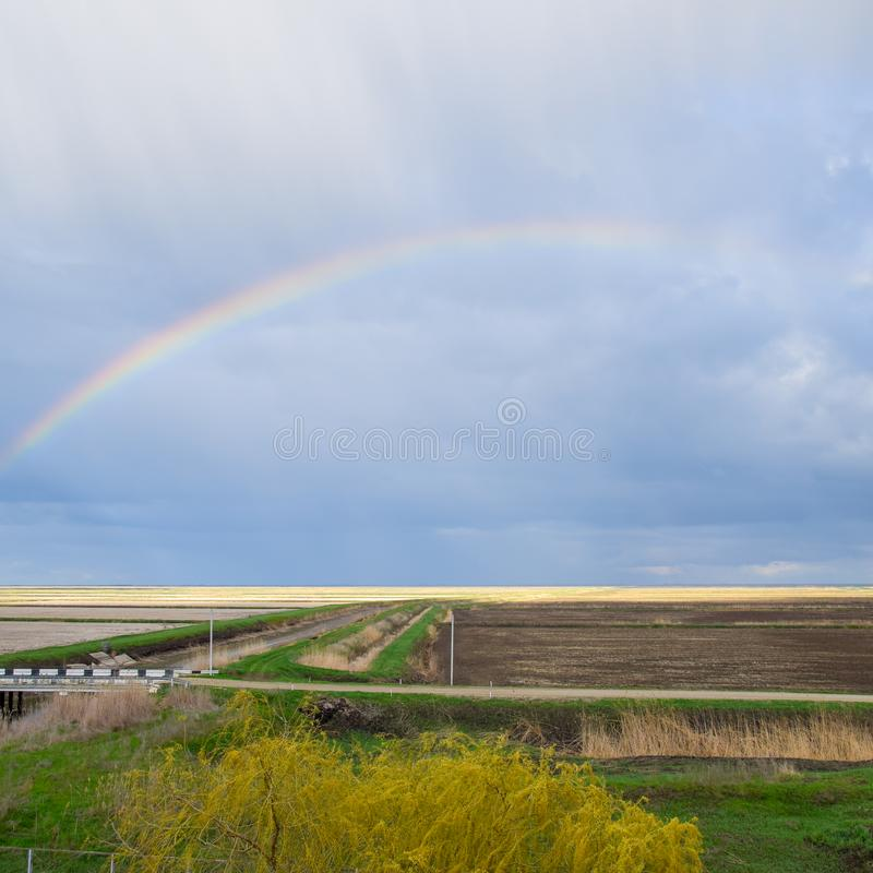 Rainbow, a view of the landscape in the field. Formation of the. Rainbow after the rain. Refraction of light and expansion in terms of spectra stock photos