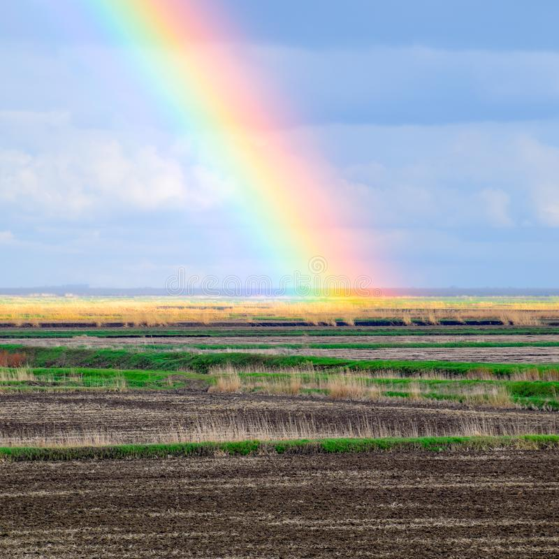 Rainbow, a view of the landscape in the field. Formation of the. Rainbow after the rain. Refraction of light and expansion in terms of spectra stock images