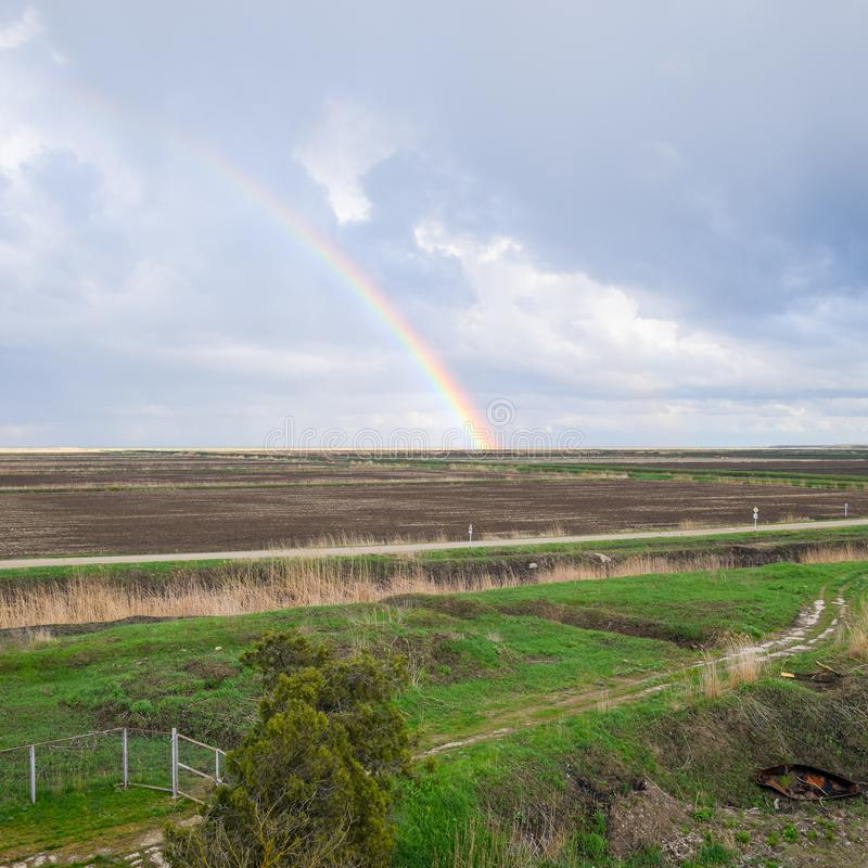 Rainbow, a view of the landscape in the field. Formation of the. Rainbow after the rain. Refraction of light and expansion in terms of spectra stock photo