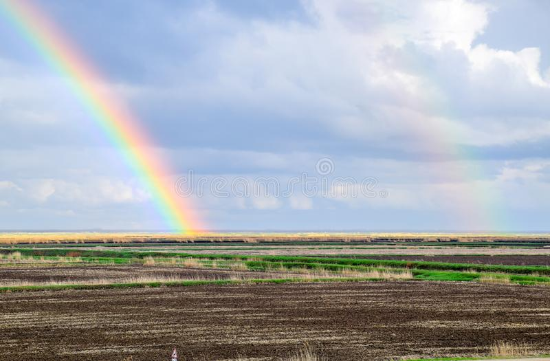 Rainbow, a view of the landscape in the field. Formation of the. Rainbow after the rain. Refraction of light and expansion in terms of spectra royalty free stock photos