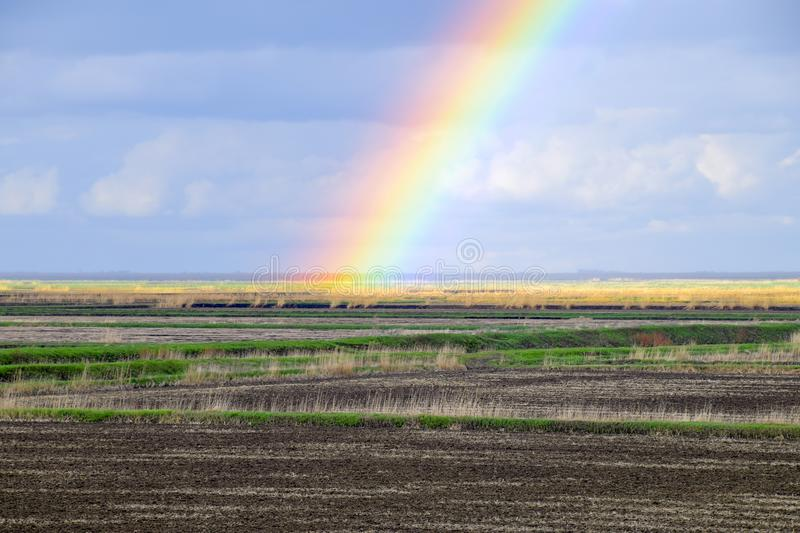 Rainbow, a view of the landscape in the field. Formation of the. Rainbow after the rain. Refraction of light and expansion in terms of spectra royalty free stock photography