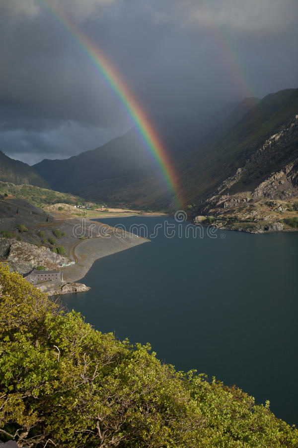 Rainbows, Llanberis pass. A view across Llyn Peris to Nant Peris and the Llanberis Pass with a double rainbow. Llanberis, Snowdonia national park, Wales, UK stock image