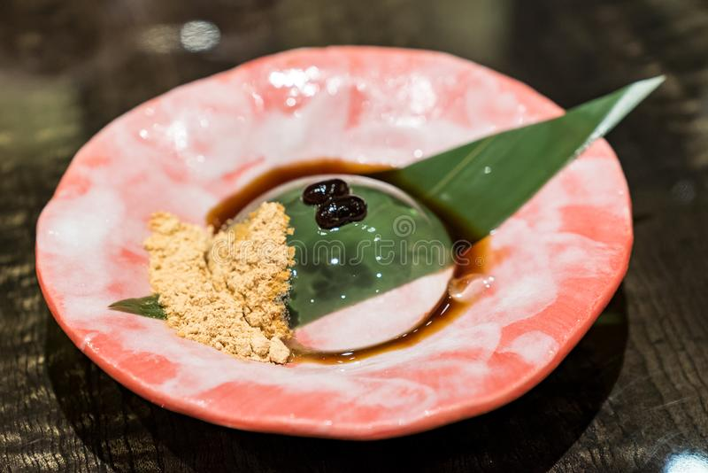 Raindrop mochi. Served with sweey black bean and soybean powder royalty free stock image