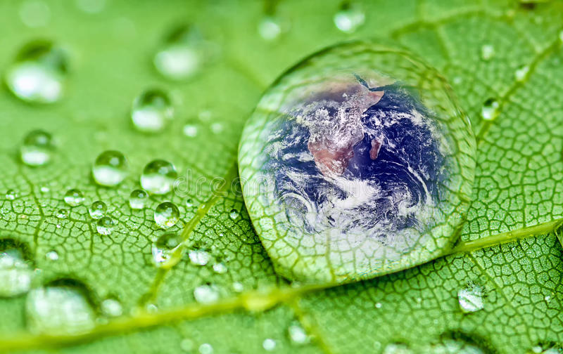 Raindrop. Planet earth inside a raindrop closeup on a green leaf (Elements of this image furnished by NASA stock photo
