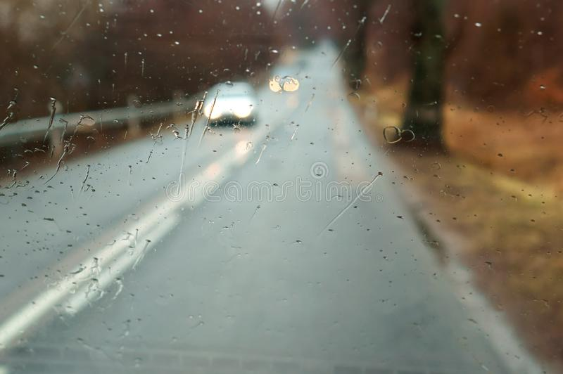 Raindrops on car glass, wet asphalt, rain on glass, drive on highway in heavy rain stock image