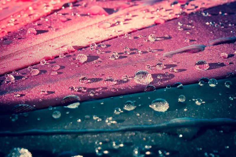 Raindrops on a colorful umbrella with all the colors of the rainbow close-up macro waterdrops background. royalty free stock photography