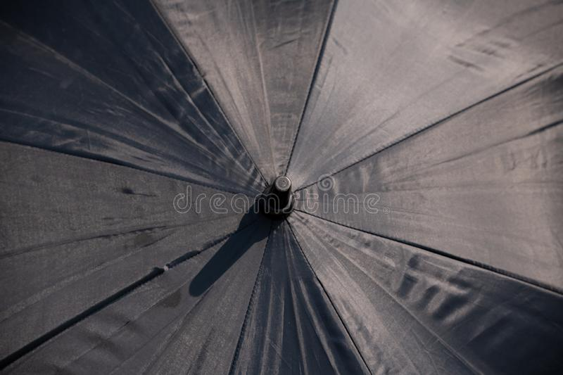 Raindrops falling on black umbrella outdoors. Description: Raindrops falling on black umbrella outdoors, background, fashion, design, abstract, frame, water royalty free stock images