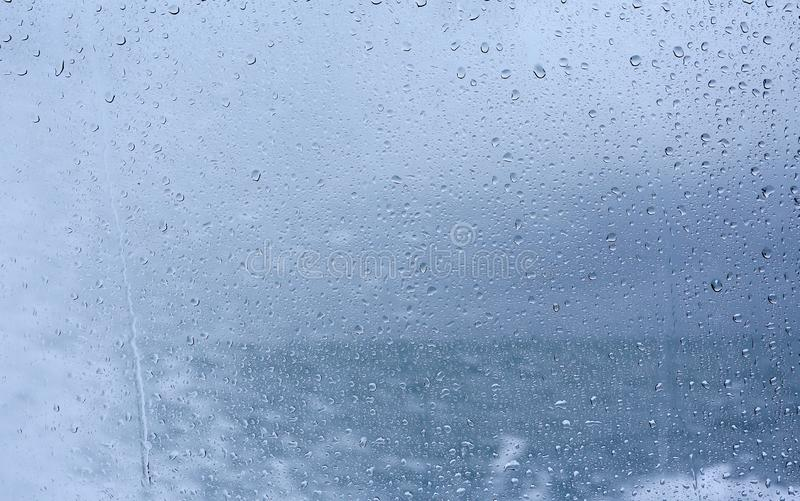 Raindrops on glass against background of sea royalty free stock image