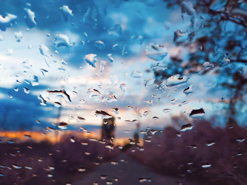 Raindrops on the glass of a car, focus on raindrops. Blurred window. Drops at sunset royalty free stock photo